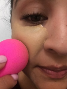 Blending the foundation into my skin using my beauty blender.